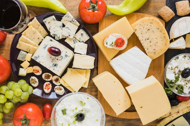 Cheese blocks and slices with tomatoes, grapes and green chili pepper on table