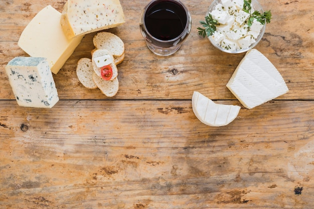 Cheese blocks with red wine and bread on wooden desk