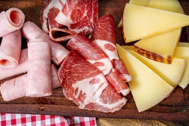 Доска сыра и мясное ассорти на деревянном столе. зенит или с высоты птичьего полета.