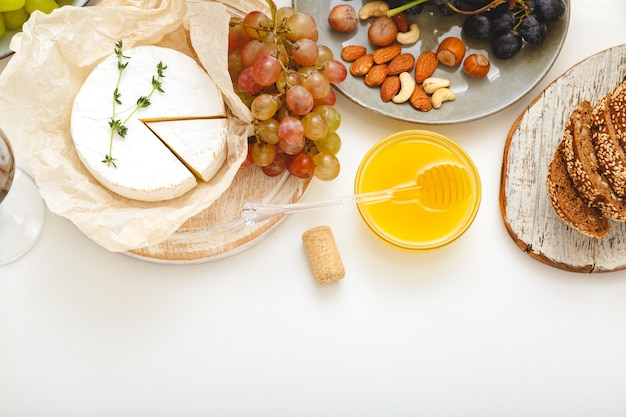 Cheese board appetizer and various delicacies snacks honey nuts grape on white table. gastronomy food. wine party mood.