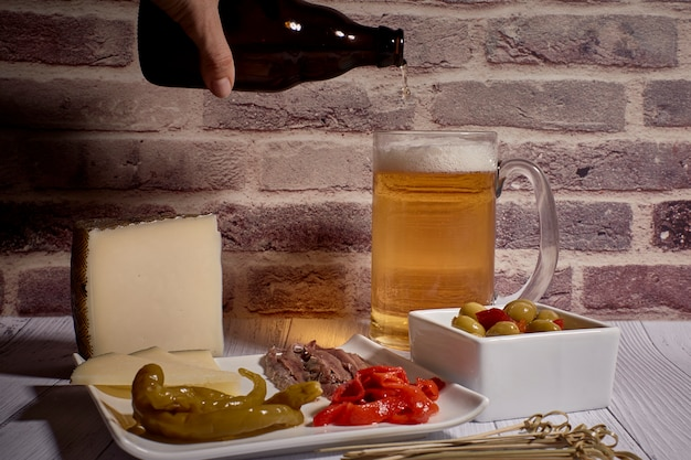 Cheese board next to a beer
