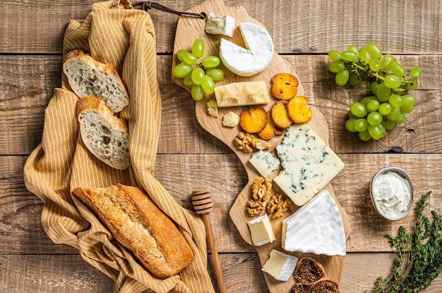 Сырная доска. бри, камамбер, рокфор, пармезан и голубой сливочный сыр с виноградом, инжиром, хлебом и орехами на деревянной доске. деревянный фон. вид сверху.