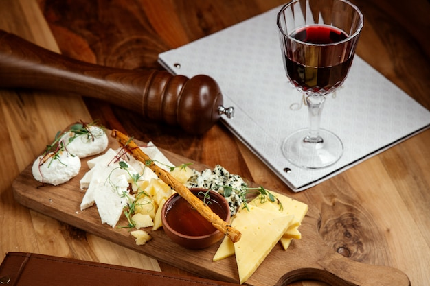 Cheese board white cheese roquefort honey and bread stick with gllass of wine on table