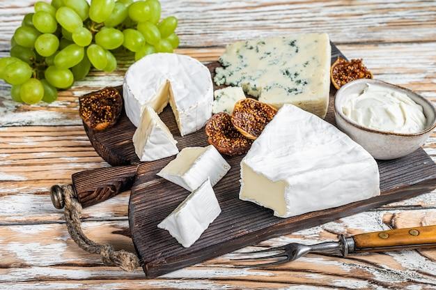 브리, 카망베르, 고르곤 졸라, 블루 크림 치즈가 들어간 치즈 보드. 흰색 나무 배경입니다. 평면도.