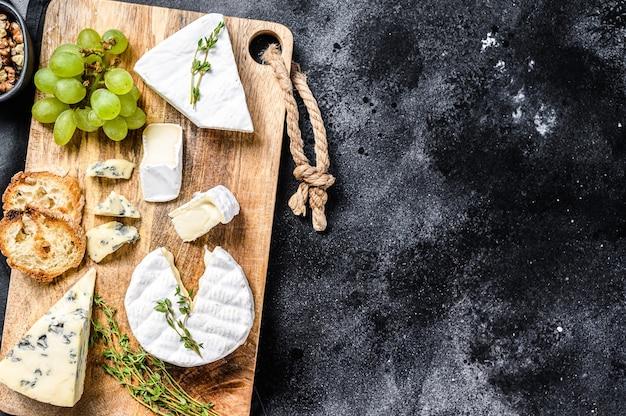 フランスのカマンベールチーズ、ブリーチーズとブルーチーズ、ブドウとクルミのチーズボード。黒の背景。上面図。スペースをコピーします。