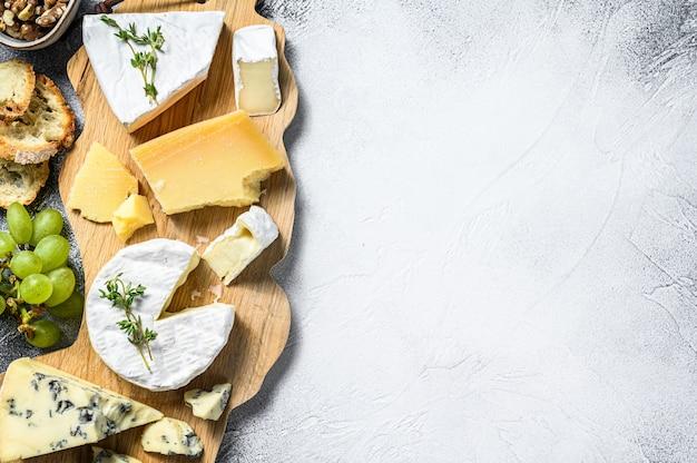 Сырная доска с французским камамбером, бри, пармезаном и голубым сыром, виноградом и грецкими орехами. белый фон. вид сверху. копировать пространство