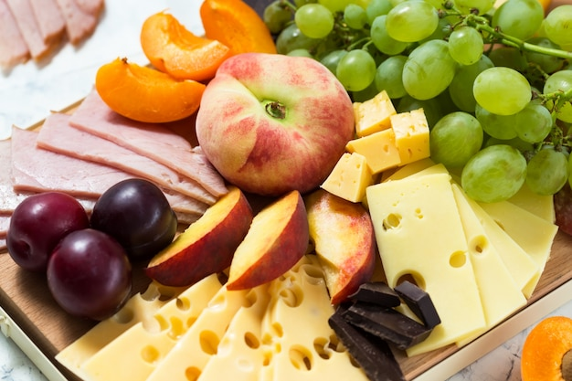 Cheese board with fruits and meat