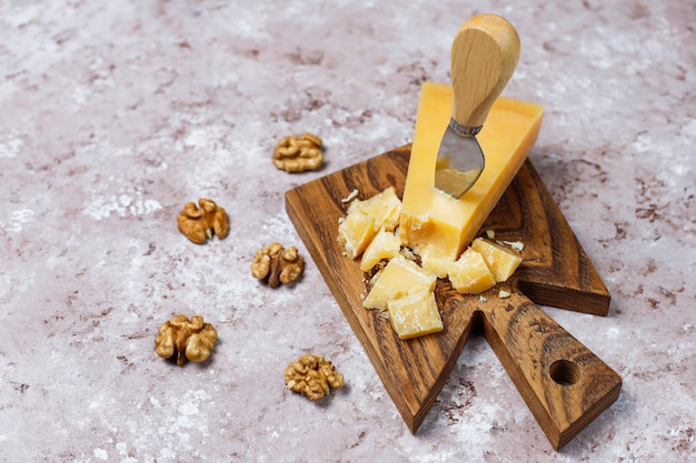 Сырная доска с твердым сыром, нож для сыра, бокал для красного вина, виноград на коричневой бетонной поверхности