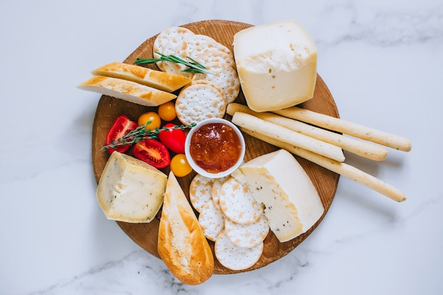 Cheese board with tomatoes, jam, baguette, bread sticks and crackers on marble background, top view