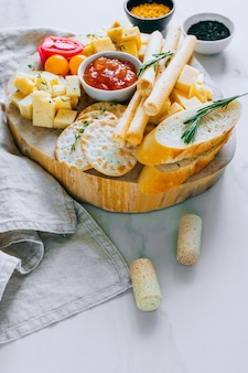 Cheese board with tomatoes, jam, baguette, bread sticks and crackers