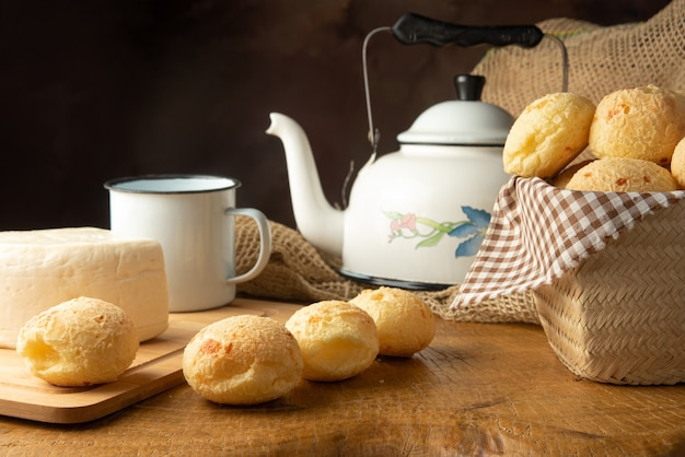 Cheese bread, brazilian breakfast arrangement, cheese bread, white cheese, kettle and accessories, dark abstract background, selective focus..