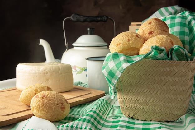 チーズパン、ブラジルの朝食の手配、チーズパン、白チーズ、やかんとアクセサリー、緑のタオル、暗い抽象的な背景、選択的な焦点。