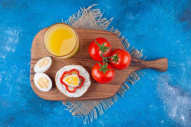 Pane al formaggio, un bicchiere di succo, uovo a fette e pomodori interi sul tagliere su pezzi di tessuto su blu.