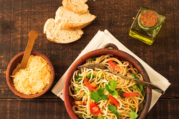 Cheese; bread and spaghetti pasta over wooden background