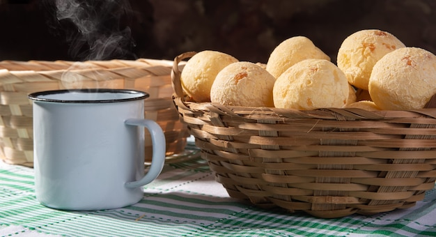 Cheese bread, straw basket full of cheese bread and a white cup on a checkered tablecloth.