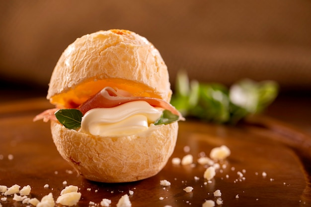 Cheese bread with cream cheese and prosciutto on wood background.