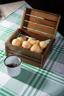 チーズパン、チーズパンが入った木製のたんす、市松模様のテーブルクロスに白いカップ。