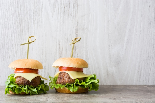Cheese burger with vegetables on wooden table copy space