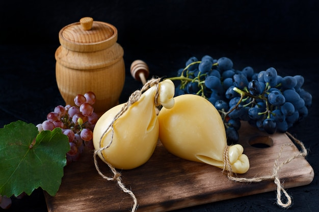 Cheese caciocavallo on a wooden board with grapes and honey on a black background. cheese pear
