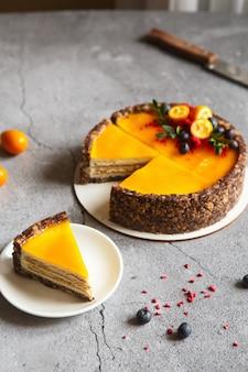 Сырный пирог с плодами манго. чизкейк с соусом из маракуйи, украшенный ягодами и фруктами