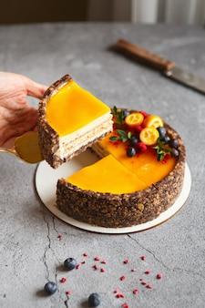 Сырный пирог с плодами манго на серой стене, украшенный ягодами и фруктами