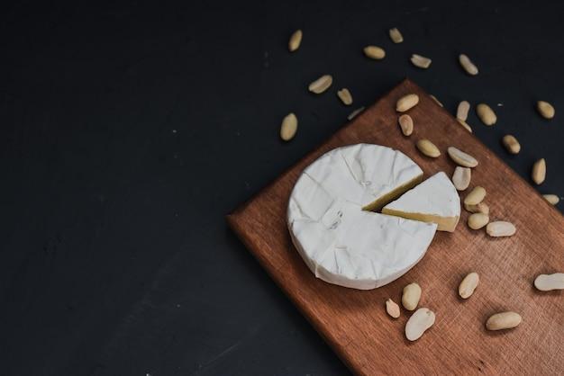 Сыр камамбер с плесенью и орехами на деревянной разделочной доске
