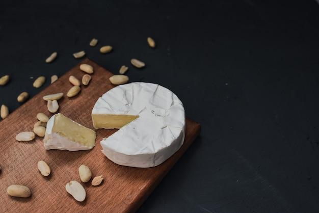 Сыр камамбер с плесенью и орехами на деревянном
