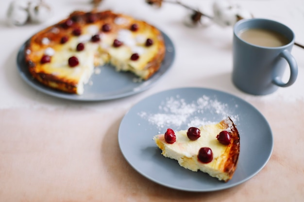 Сырная запеканка с ягодами и чашкой кофе на вид сверху