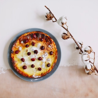 Cheese casserole with berries on kitchen table top view