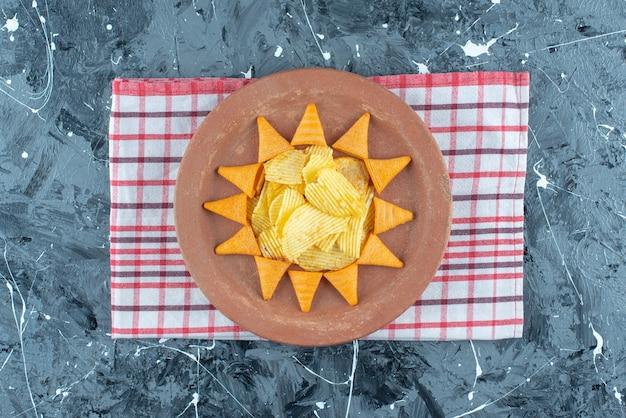 대리석에 티 타월에 접시에 치즈 칩과 콘 칩.