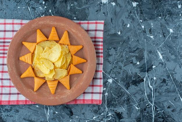 대리석 테이블에 티 타월에 접시에 치즈 칩과 콘 칩.