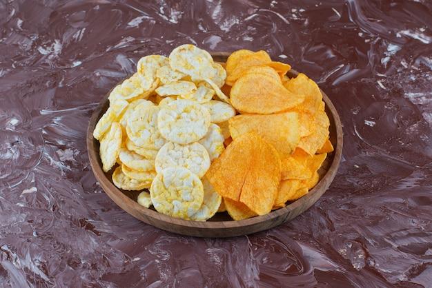 대리석 표면에 접시에 치즈 칩과 감자 칩