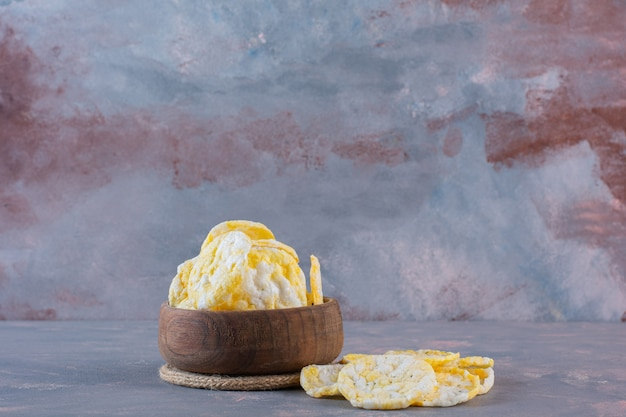 Cheese chips in a bowl , on the marble background