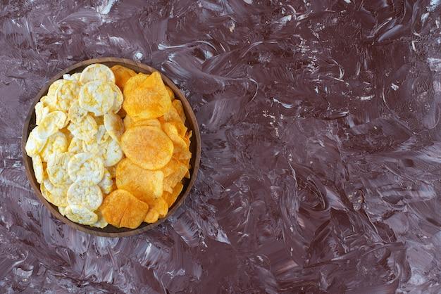 Chip di formaggio e patatine fritte nel piatto su marmo.