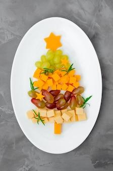 Рождественская елка сыра со свежим виноградом и розмарином на белой тарелке на бетонном фоне. идея еды на рождество и новый год. вид сверху.