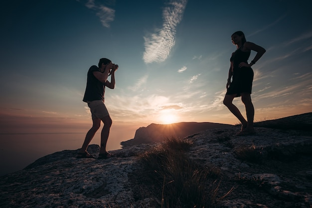 チーズ。ピクニック中にガールフレンドの写真を撮る集中男性。もう一発。最愛の人と一緒に旅行してください。山をハイキングするのが大好きなカップル。夏休みのコンセプト。
