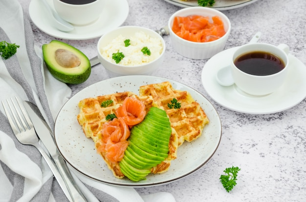 Cheese crispy waffles with cream cheese, smoked salmon and avocado for breakfast with a cup of coffee on a light stone background.