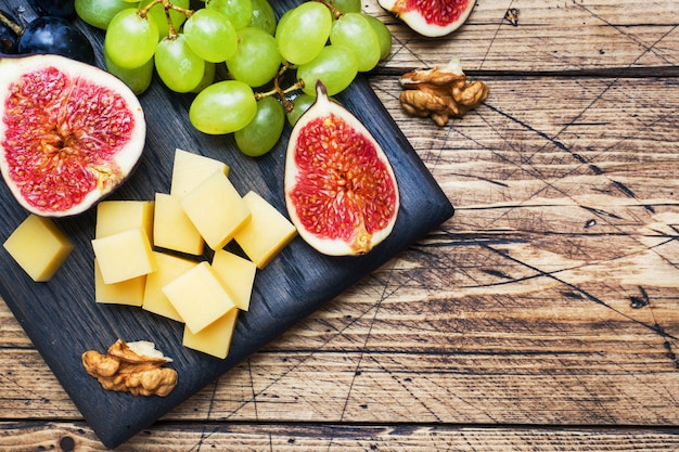 Сырные кубики, свежие фрукты, инжир, виноград медовый орех на деревянной разделочной доске. копировать пространство
