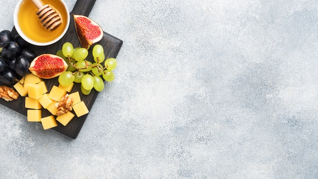 Cheese cubes, fresh fruit figs grapes honey walnut on wooden chopping board. copy space.