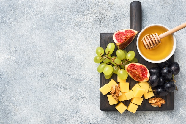 Cheese cubes, fresh fruit figs grapes honey walnut on wooden chopping board. copyspace.