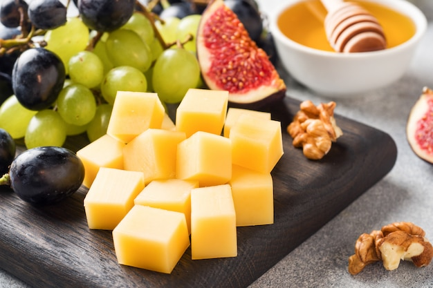 Cheese cubes, fresh fruit figs grapes honey walnut on wooden chopping board. selective focus. close up.
