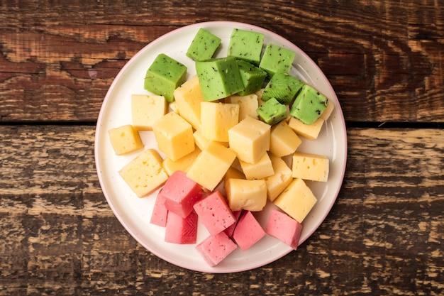 プレート上の緑、黄、赤のチーズキューブ、ワインの前菜。上を表示します。閉じる
