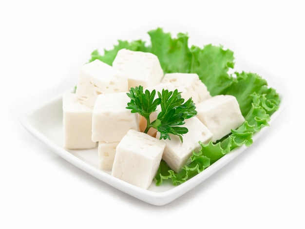 Cheese cubes on a plate with lettuce leaves