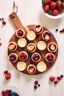 Cheese cupcakes with fruit jelly and fruits on a wooden plate