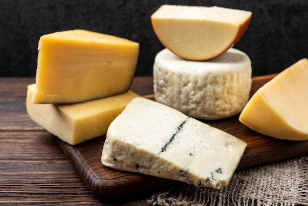 Cheese on dark wooden background.