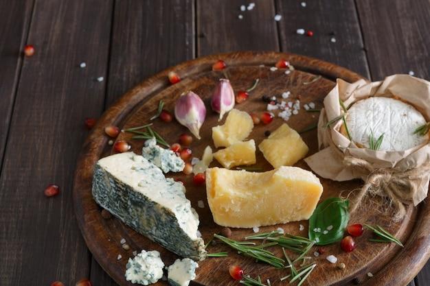 Деликатесен с сыром крупным планом на деревенском дереве, голубом рокфорте и пармезане
