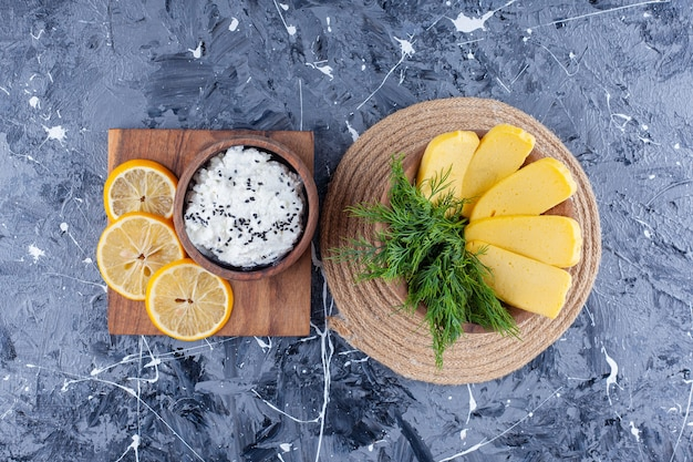 Cheese and dill in a bowl on a trivet next to a bowl of cheese and sliced lemon on a board , on the blue surface.