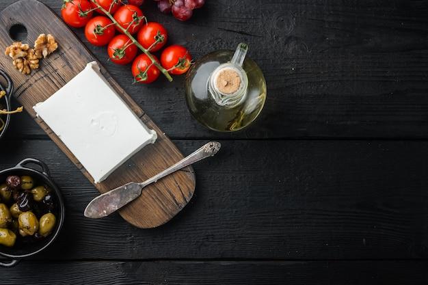 검은 나무 테이블에 치즈 죽은 태아의 그리스 샐러드 재료, 평평하다