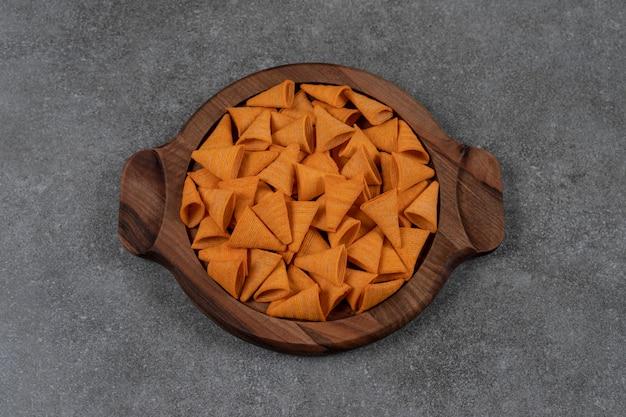 Chips di mais a forma di cono aromatizzato al formaggio nel piatto di legno sulla superficie di marmo