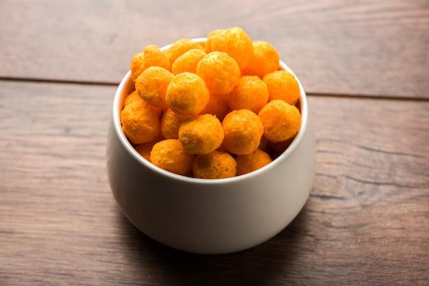 チーズ風味のパフまたはボールのクローズアップ、ボウルまたは不機嫌そうな背景の上で提供